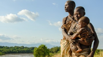 Ethiopia: Lower Omo River Basin, Kotrouru, a Kwego village, three generations: infant, a pregnant mother, older woman, standing on bank overlooking Omo River